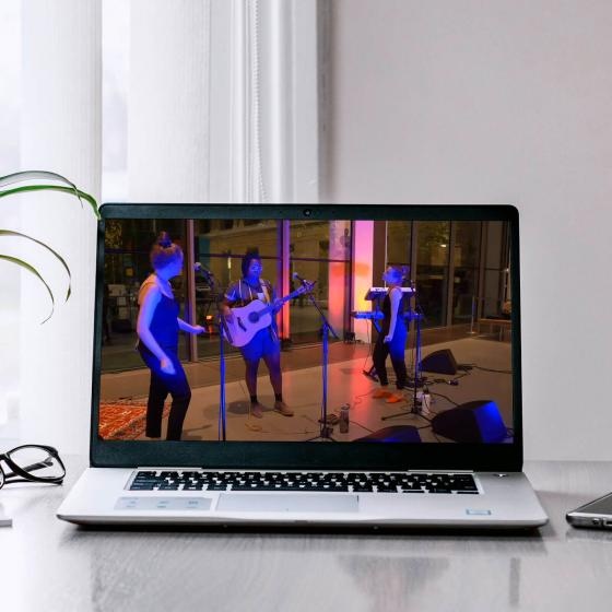 laptop playing video of musicians performing on stage for concert