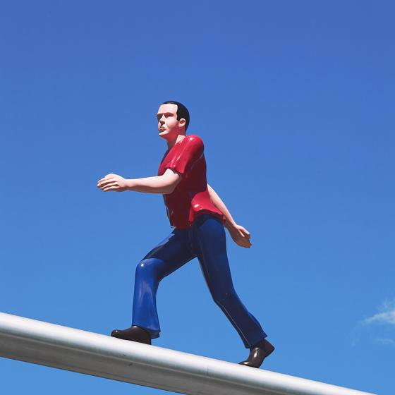 Sculpture of a man wearing a red t-shirt and blue pants walking on a pole.