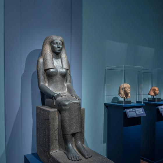 Ancient Egyptian statue of a woman sitting against a blue wall next to cases with sculptures of heads.