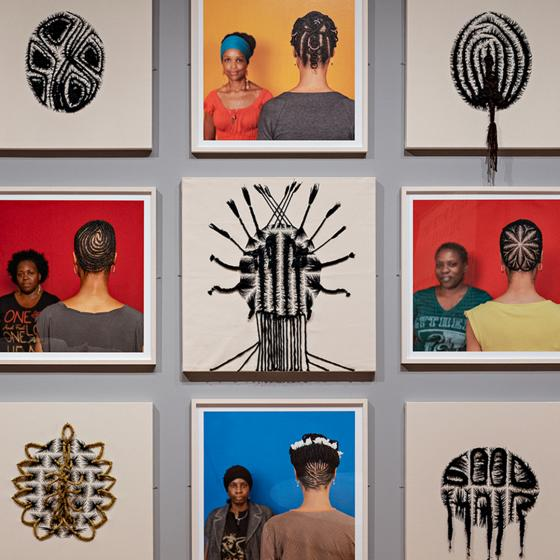 Photograph of a grid of 12 artworks on display in a gallery