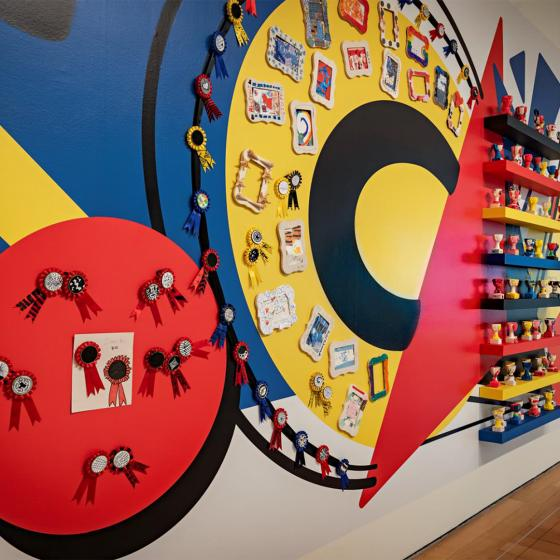 A red, blue, and yellow mural with small frames and sculptures hung against it.