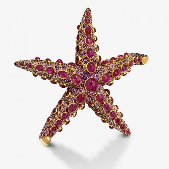 A gold, pink, and purple starfish made out of jewels.