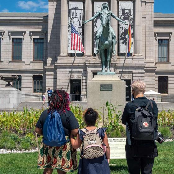 Three people stand with their backs to the camera looking at a sculpture of a Native American man on horseback.