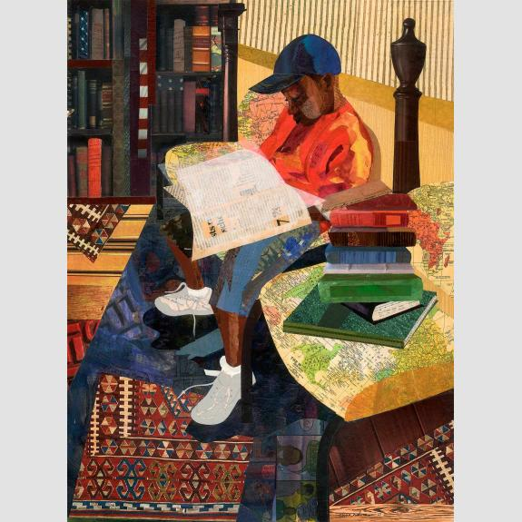 Young boy sitting reading indoors.