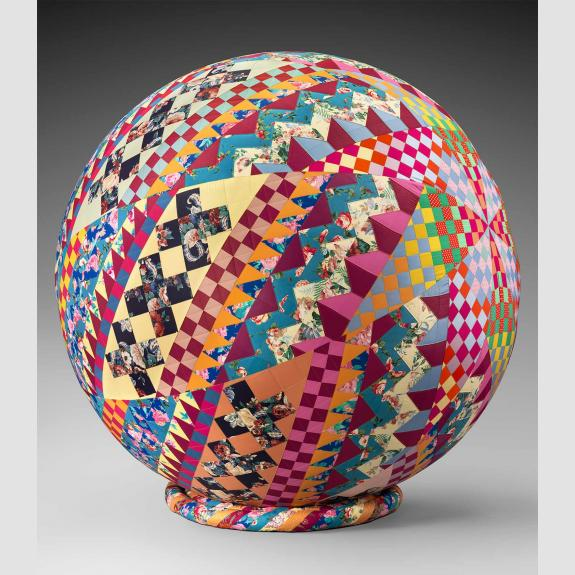 A multi colored quilt wrapped around a spherical ball