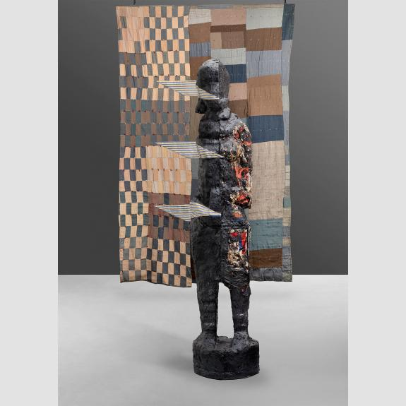 Quilt with tan, blue and brown squares and rectangles with a sculpted figure in front of it.