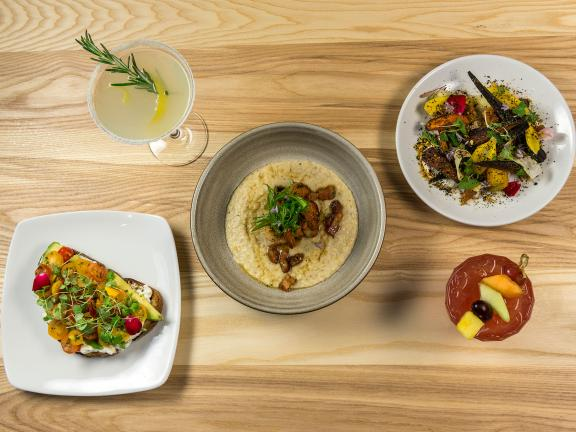 Variety of dishes spread out on wooden table in 465 Restaurant and Bar