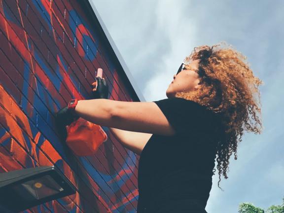 Sneha Shrestha working on a mural