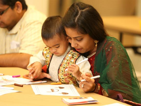 Kid held by parent drawing during Diwali event