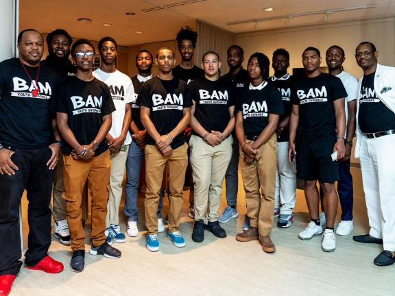 Members of BAM (Becoming a Man), all wearing BAM T-shirts, pose with mentors