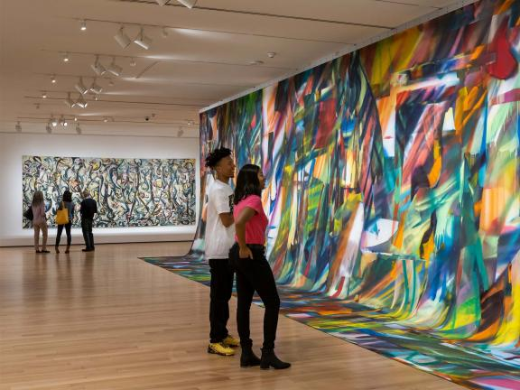 People looking at Mural, by Jackson Pollock, and Untitled by Katharina Grosse