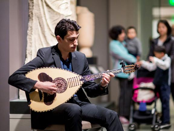 Lute player performing in Ancient Greece gallery, family with stroller watching in background