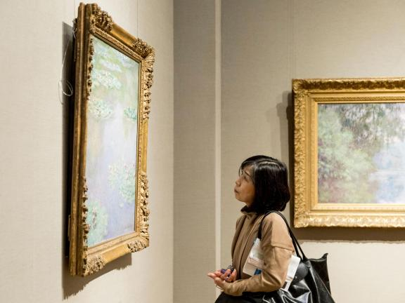 Visitor in Monet gallery looking at painting on wall