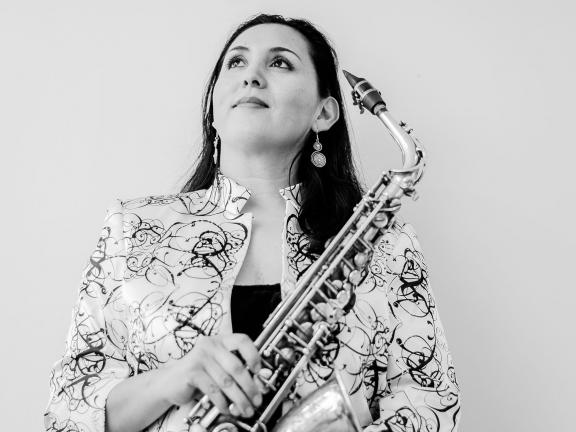 black and white photo of musician Patricia Zárate-Pérez with her saxophone