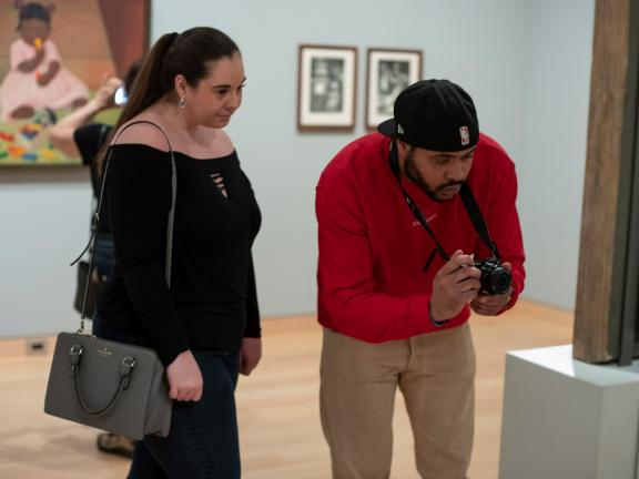 Two visitors looking at object in American gallery, one hunched over pointing camera at object