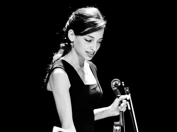 Black and white photograph of Ceren Turkmenoglu looking downward while holding her violin and bow in her left hand.