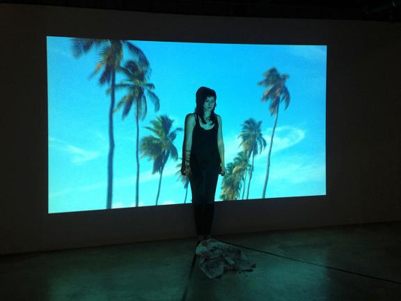 artist standing in front of projected screen of palm trees