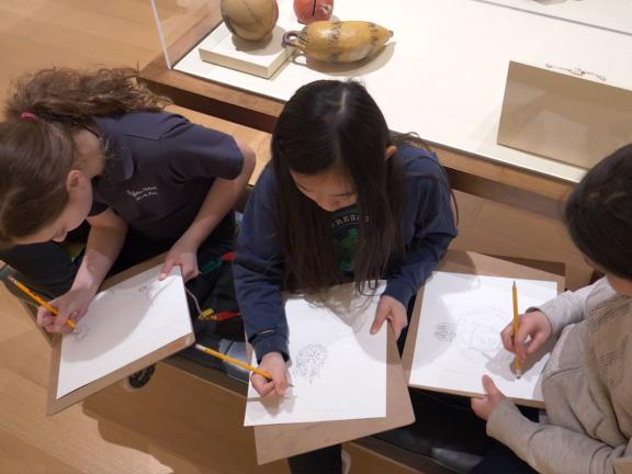 Students sketching on bench in Native North American Art gallery