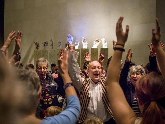 Visitors dancing with arms in the air during Hanukkah celebration in Shapiro Family Courtyard
