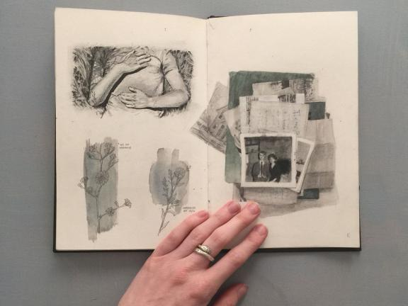 Photograph of artist hand holding open book featuring black and white drawings