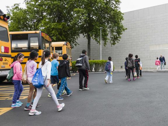Line of students walking towards group entrance from parked buses