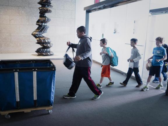 Student walking in through group entrance, about to drop off bag in bin