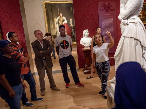 Group of students with teacher looking up at sculpture in Salon gallery