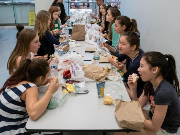 Students sitting at table eating lunch