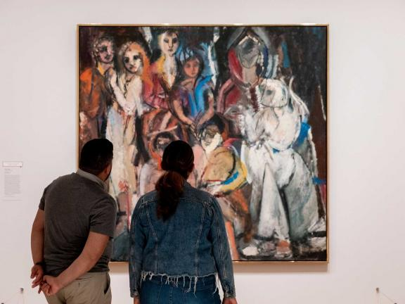 Visitors standing in front of an abstract oil painting of women by Grace Hartigan titled Masquerade