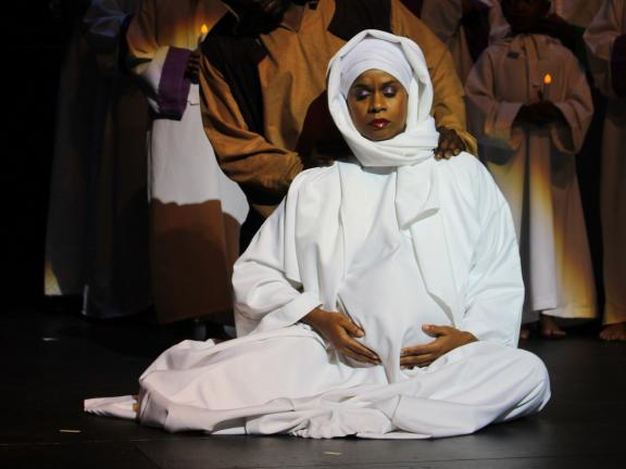 Black Nativity performance featuring woman dressed as religious figure surrounded by people