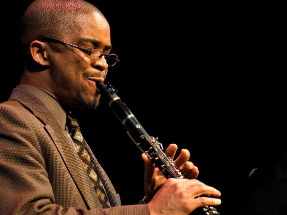 Profile of Darryl Harper in jacket and tie playing clarinet