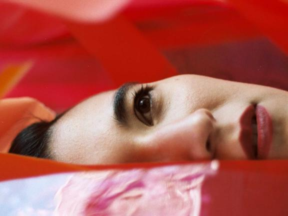 Vocalist Stephanie Lamprea lies on her right side atop a red tarp, a third her face hidden.