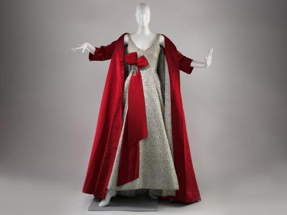 Mannequin wearing a silver floor length v-neck dress with red cape and red bow at waist
