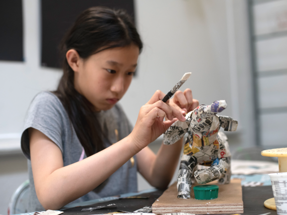 young female student making paper mache sculpture