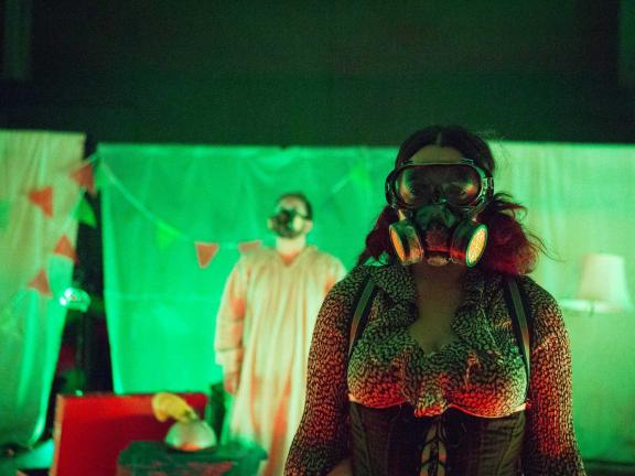 Two people wearing gas masks, a corseted person in the foreground and a person in a gown in the background, stand facing the camera.
