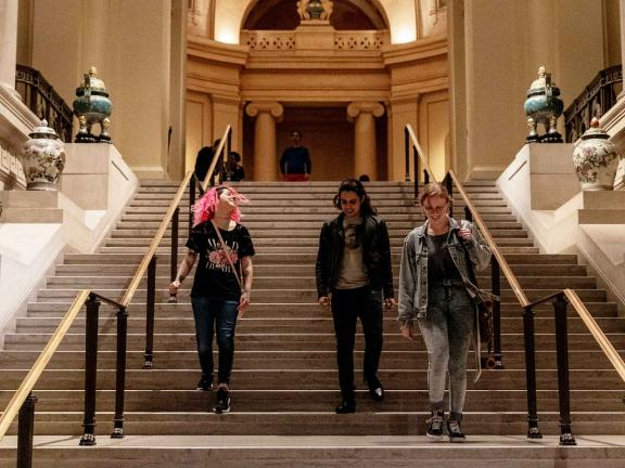 group of young people walking down elaborate stairs