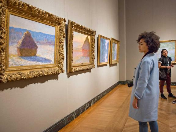 girl in blue coat looking at paintings by Monet