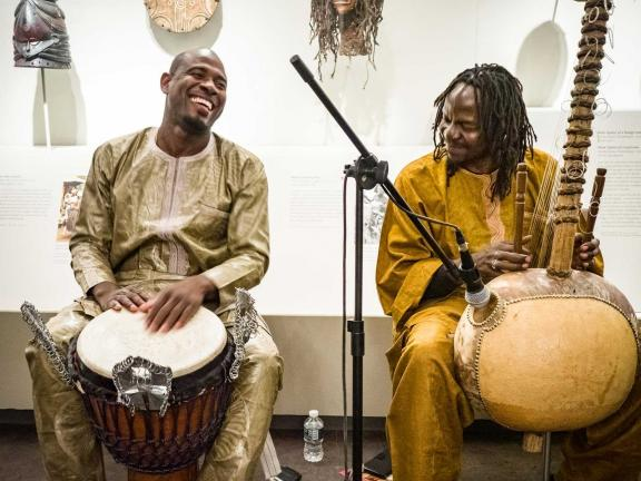 Two musicians playing instruments in gallery, drum on left, kora on right