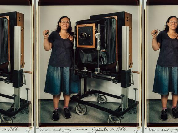 self-portrait of Elsa Dorfman standing next to huge camera on cart