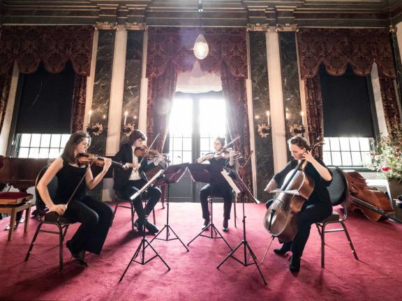 4 string instrumentalists perform in a large, opulent gallery space.