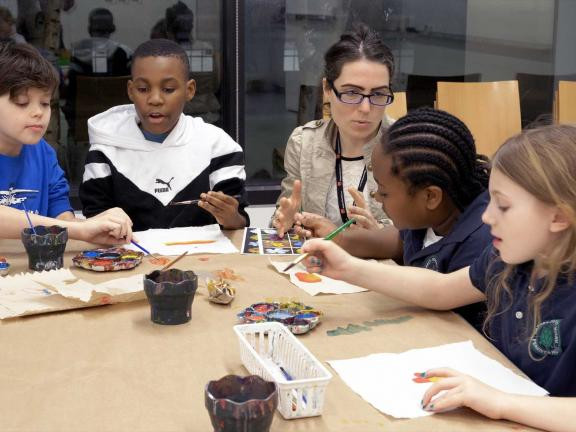 instructor sitting at table with kids working on art project