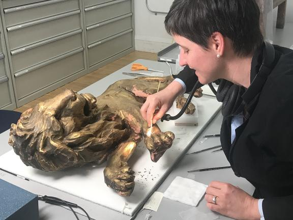 Conservator consolidating gilding on a sculpture of a lion