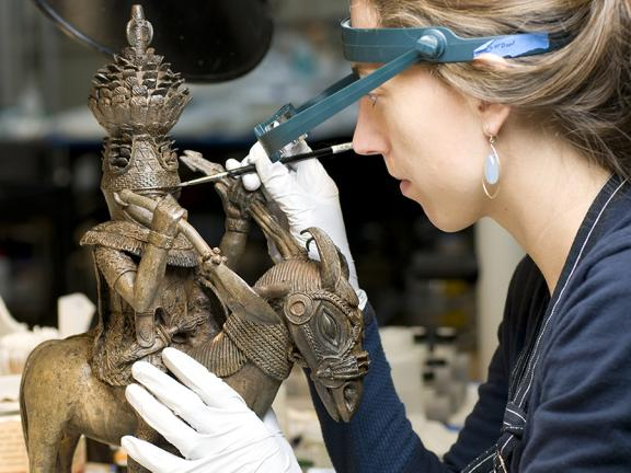 Conservator toning the surface of a copper alloy figure