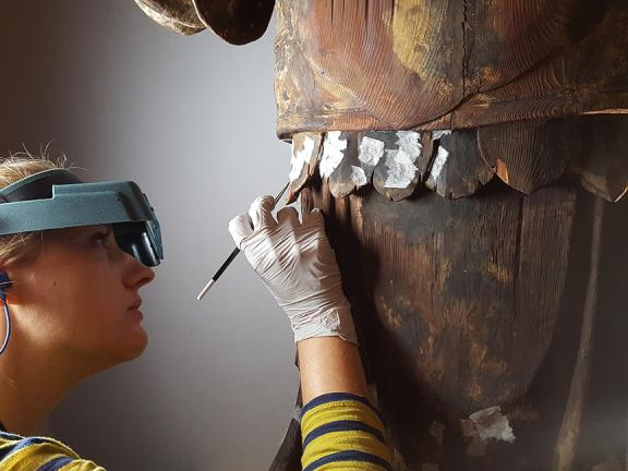 Conservator consolidating pigment on a woodblock construction sculpture