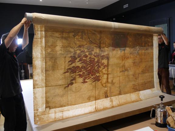 Conservators moving an oversized Chinese painting