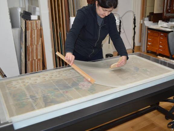 Conservator brushing the facing layer onto a Japanese painting