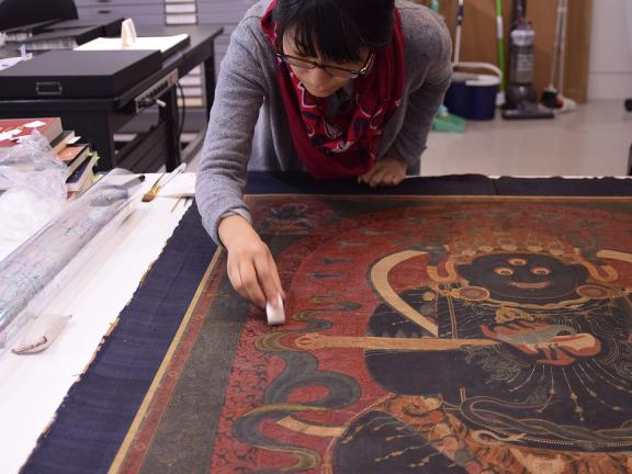 Conservator cleaning surface of a Tibetan painting