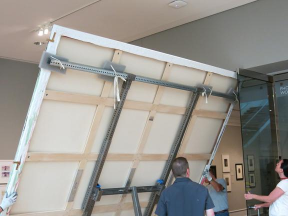 Collections care staff move an oversized painting on a custom-built truck