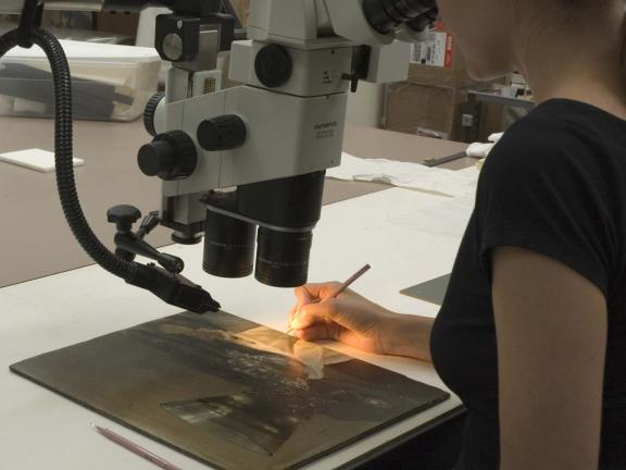 Conservator taking a sample under microscope