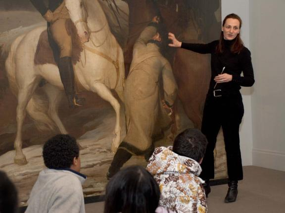 Conservator interacting with students in front of a painting